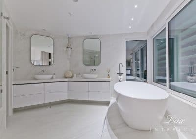 wide shot of the bathroom with the tub, window views and french shutters