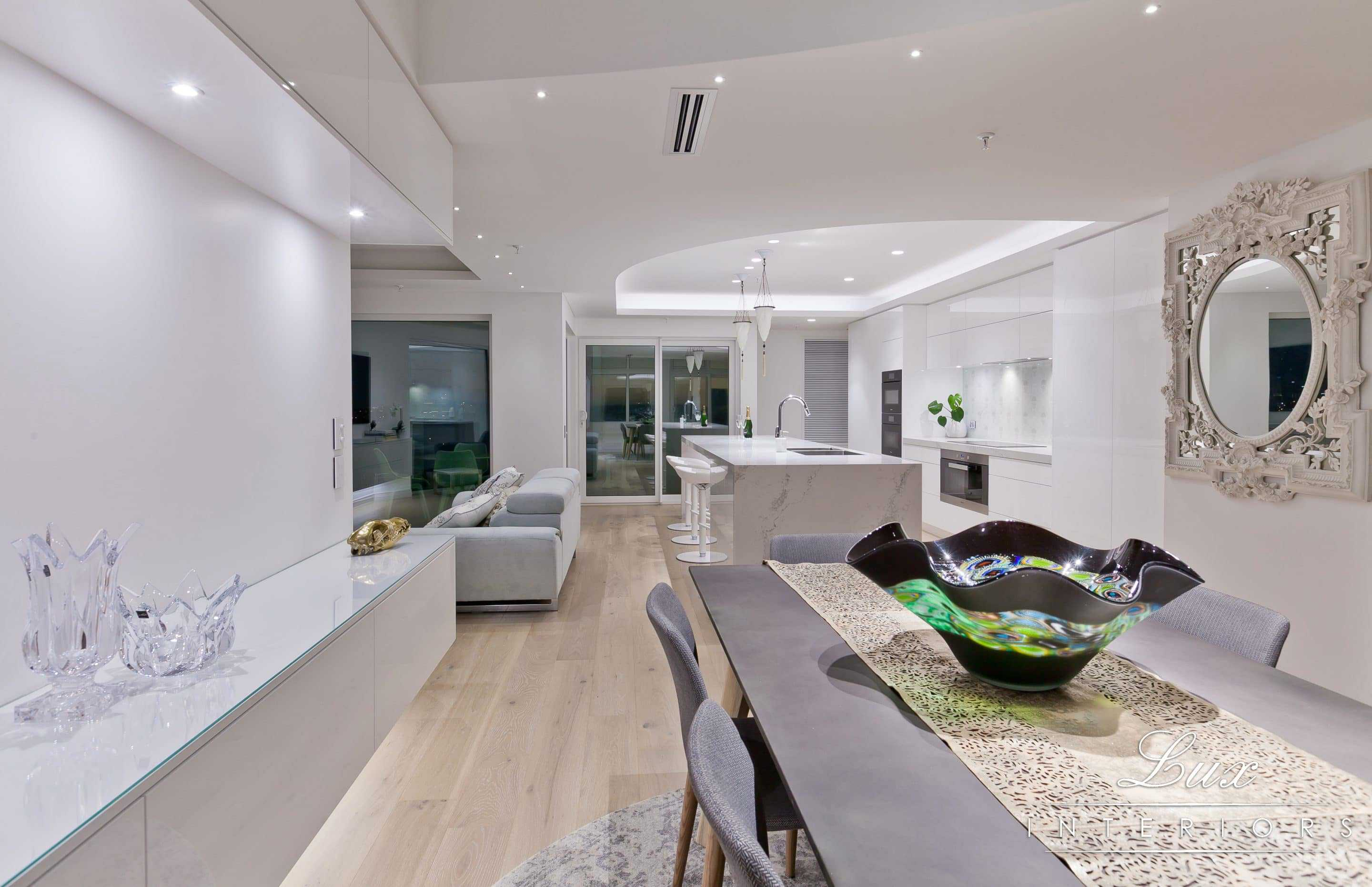 intricate details of the benchtop in the dining room with shot of kitchen and lounge