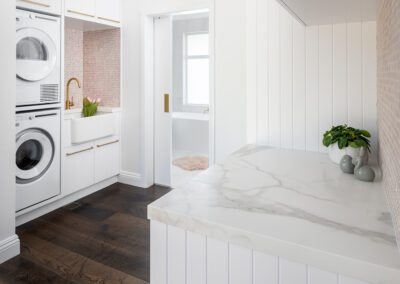 North Beach Coastal Barn Laundry Renovation with brass, white V Groove panelling and pink penny round tiles