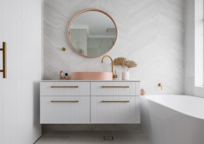 North Beach Coastal Barn Bathroom with brass tapware, pink concrete basins, V Groove panelled cabinetry and Onyx stone look tiles with a feature chevron pattern